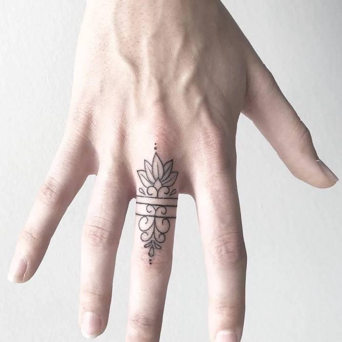 tatuaggio femminile nero su dito medio